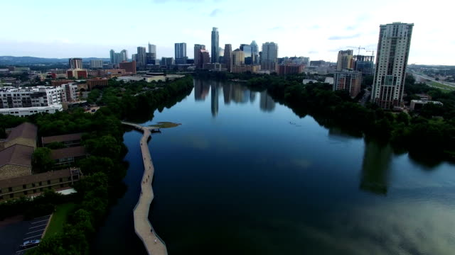 vídeos de stock e filmes b-roll de aerial view of austin , texas , usa above calm blue town lake with pedestrian bridge modern curved route below and reflection of the skyline in the background - town