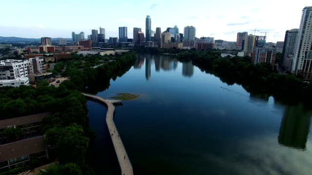 Aerial View of Austin , Texas , USA above Calm Blue Town Lake with Pedestrian Bridge modern curved route below and reflection of the Skyline in the background closer
