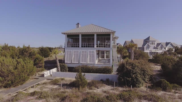 drone. aerial view of back porch of luxury two-story seaside bald head island beach house with dock leading to the beach on a sunny summer day. - beach house stock videos & royalty-free footage