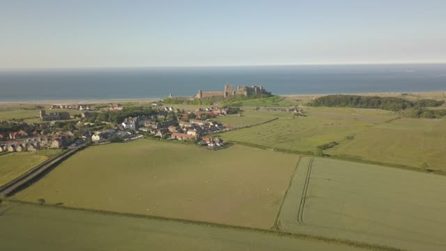 aerial view of bamburgh castle with north sea in background, northumberland, england, united kingdom, europe - newcastle upon tyne inghilterra video stock e b–roll