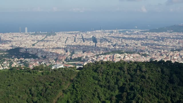 aerial view of barcelona skyline with mountains in foreground - finding stock videos and b-roll footage