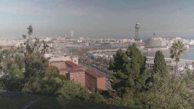 vídeos de stock e filmes b-roll de aerial view of barcelona with cable car tower, barceloneta district and port vell harbour. - porto de barcelona