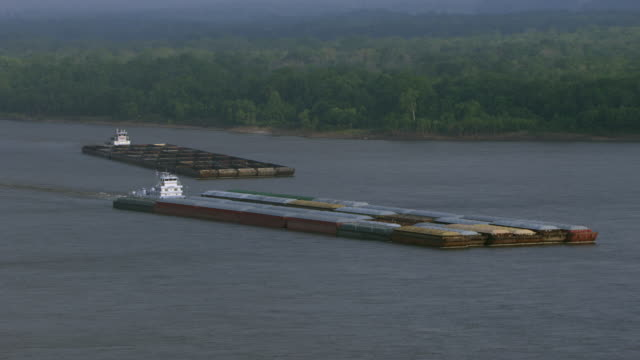 vidéos et rushes de aerial view of barge in mississippi river with tree covered landscape, arkansas. united states of america - remorqueur