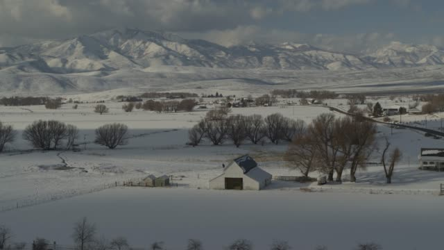 stockvideo's en b-roll-footage met aerial view of barn and houses in valley near mountain range in winter / wallsburg, utah, united states - boerderijschuur