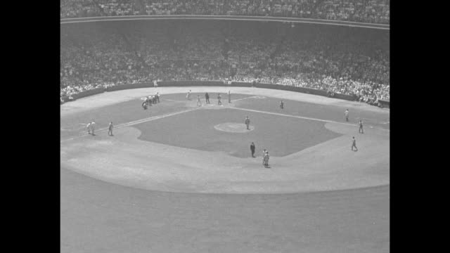 Aerial view of baseball diamond with player scoring during the AllStar Game / Babe Ruth swings homers for the American League / view of packed...