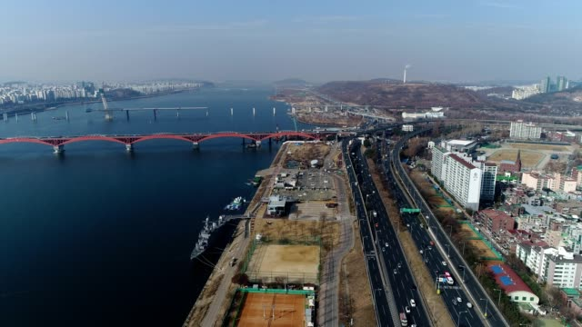 vídeos y material grabado en eventos de stock de aerial view of battleship park (the first shipbuilding theme park) and seogang bridge in seoul at daytime - anclado