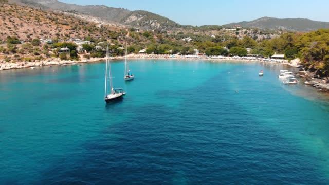 ギリシャの島、ヨット、ターコイズブルーの海を持つ海岸線の湾と美しいビーチの空中写真 - 地中海点の映像素材/bロール
