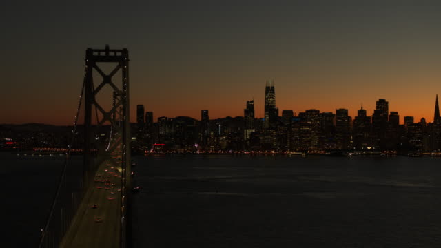 aerial view of bay bridge and city skyline at sunset / san francisco, california, united states - distant stock videos & royalty-free footage