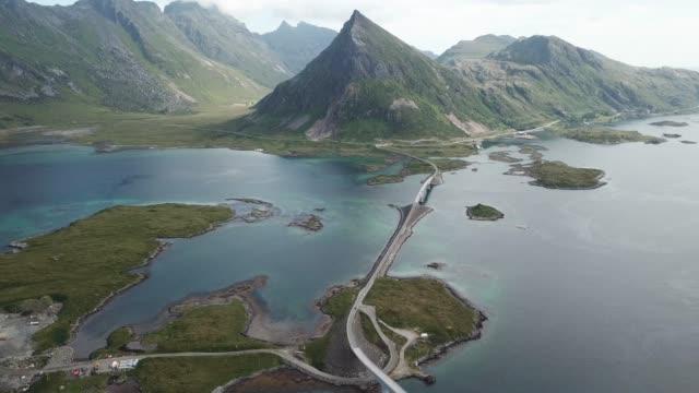 stockvideo's en b-roll-footage met luchtfoto van de prachtige brug en de weg boven de zee en de bergen in noord-noorwegen - kust karakteristiek