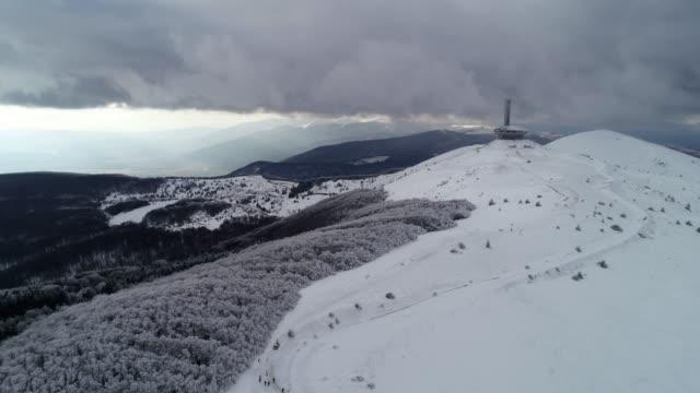 Luftaufnahme des schönen, dramatisch, schnell bewegte Wolken über einem Berggipfel im Winter, Science-Fiction-Stimmung, Buzludzha Denkmal, UFO, der Stern erhebt sich über dem Nebel, Fernweh