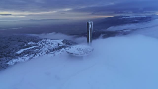 aerial view of beautiful, dramatic, fast moving clouds over a mountain peak in the winter, science fiction mood, buzludzha monument, ufo, the star rising above the fog, wanderlust - monument stock videos & royalty-free footage