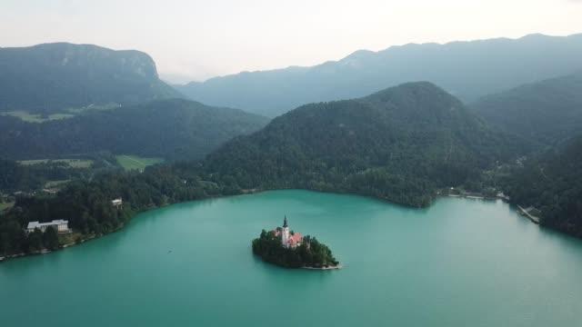 stockvideo's en b-roll-footage met luchtfoto van het prachtige meer van bled met klein eiland en kerk op het tijdens zonsondergang - julian alps