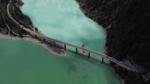 aerial view of beautiful mountain lake, bridge and forest in bavarian alps - concrete stock videos & royalty-free footage