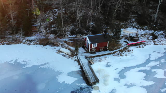 aerial view of beautiful red cottage with sauna, pier and frozen lake in sweden. - サウナ点の映像素材/bロール