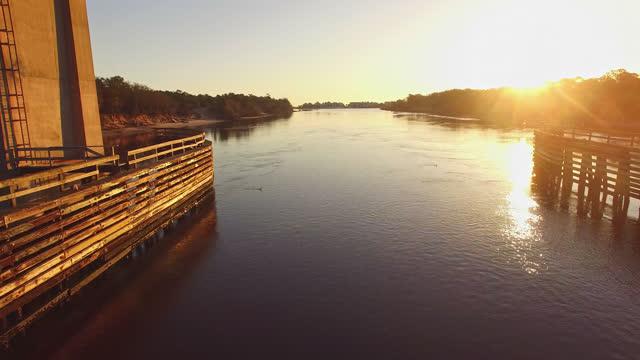 drone. aerial view of beautiful sunrise passing through snows cut bridge and over canal near carolina beach - carolina beach stock videos & royalty-free footage