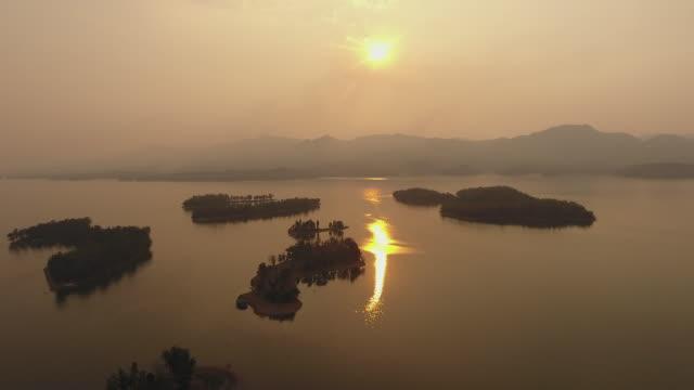 夕暮れ時の小さな島々を持つ美しい熱帯湖の空中写真 - リフレクション湖点の映像素材/bロール