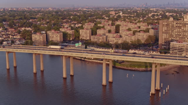 aerial view of beechhurst residential neighborhood in queens with the remote view of manhattan in the backdrop over throgs neck bridge at sunrise. drone video footage with the cinematic panoramic-orbit camera motion - bronx stock videos & royalty-free footage