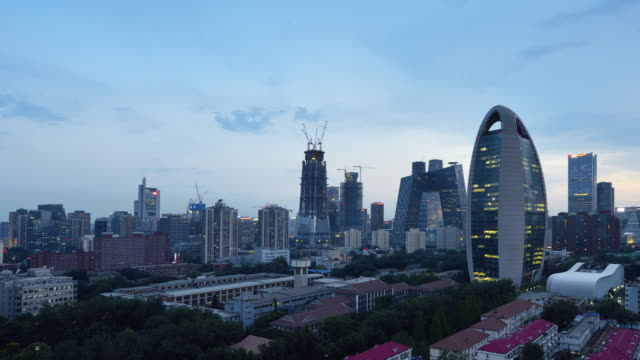 Aerial View of Beijing City Skyline and CCTV Headquarters, Day to Night Transition, Panning