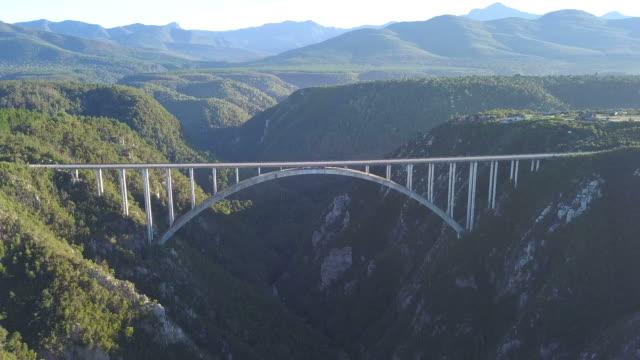 vídeos de stock e filmes b-roll de aerial view of big bridge over a valley - república da áfrica do sul