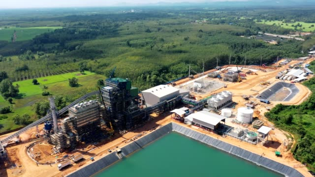 aerial view of biomass power plant with storage of wooden fuel against blue sky - storage compartment stock videos & royalty-free footage