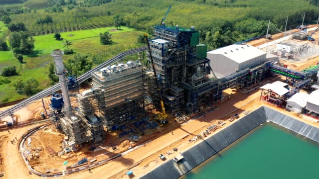 aerial view of biomass power plant with storage of wooden fuel against blue sky - boiler stock videos & royalty-free footage