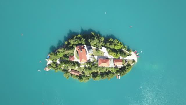 vídeos de stock e filmes b-roll de aerial view of bled island, slovenija - lago bled