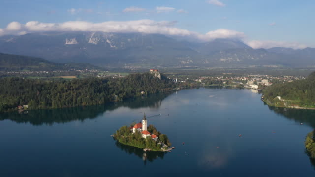 aerial view of bled lake, flying over the bled island and the famous church at dusk - lake bled stock videos & royalty-free footage