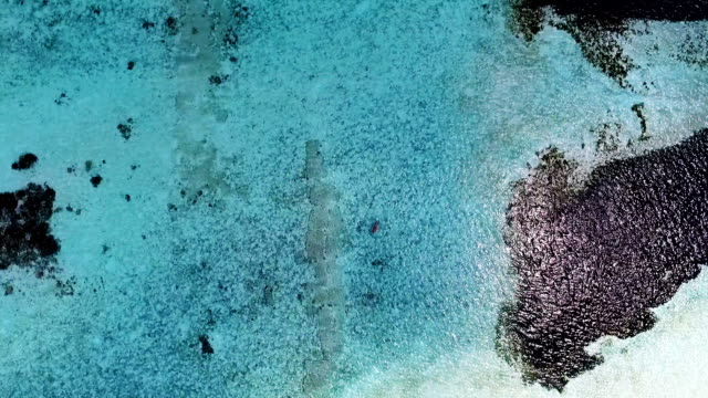 Aerial view of blonde girl diving on Maldives