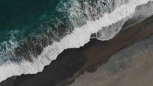 aerial view of blue waves crashing onto black sand beach - black sand stock videos & royalty-free footage