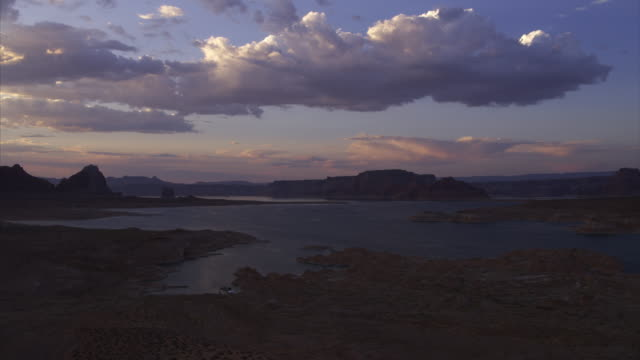 aerial view of boat in lake near rock formations at sunset / lake powell, arizona, united states - lake powell stock videos and b-roll footage