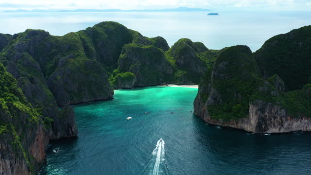 aerial view of boat sailing into phi phi le, phi phi islands, thailand - phi phi le stock videos & royalty-free footage