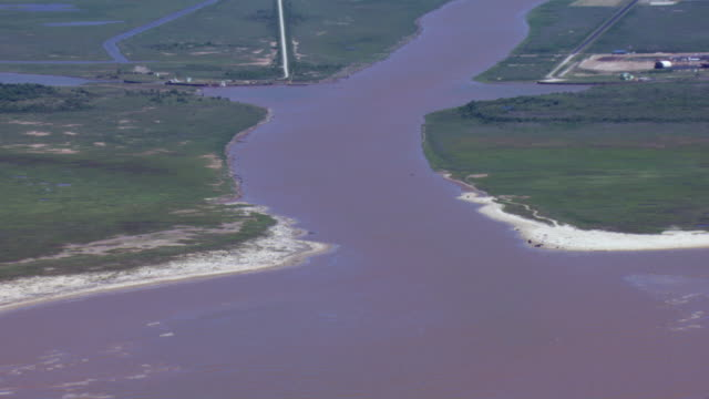 aerial view of brazos river emptying into the gulf of mexico near freeport, texas. - estuary stock videos & royalty-free footage