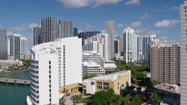 vidéos et rushes de vue aérienne de brickell key island, downtown miami, floride, par une journée ensoleillée. clip vidéo réalisé par drone avec mouvement de caméra de recul et ascendant, survolant l'île. - miami