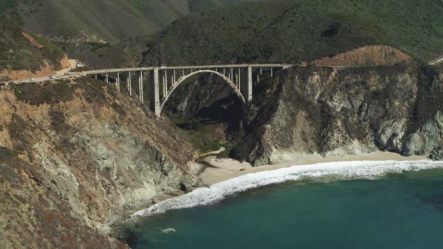 aerial view of bridge at rocky coast near ocean waves / big sur, california, united states - bixby creek bridge stock videos & royalty-free footage