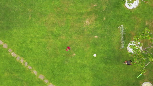 aerial view of brothers playing football in garden - domestic garden stock videos & royalty-free footage