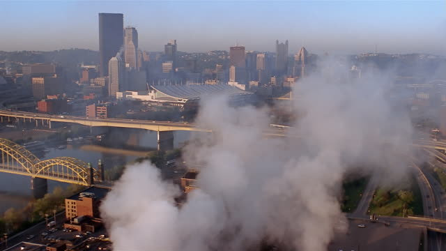 vidéos et rushes de aerial view of buildings and freeway through cloud of pollution / tilt down view of factory smokestack - pennsylvanie
