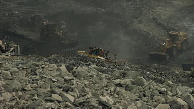 vídeos y material grabado en eventos de stock de aerial view of bulldozers and front loaders at mountaintop mine - coal mine