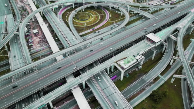 aerial view of busy city traffic at an intersection on a major freeway in bangkok, thailand - major road video stock e b–roll