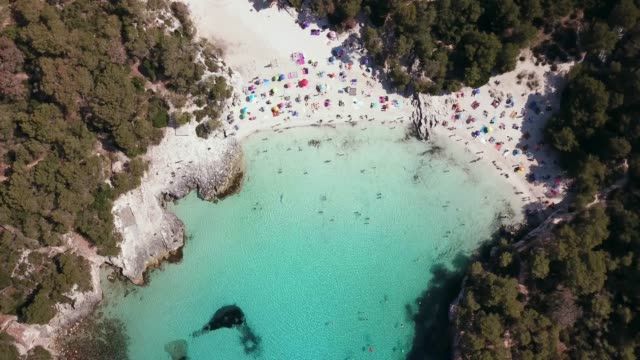 aerial view of cala turqueta beach crowded with people - turquoise coloured stock videos & royalty-free footage