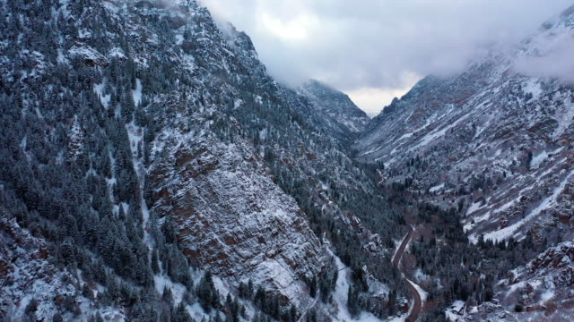 aerial view of canyon covered in snow flying over road - canyon stock videos & royalty-free footage