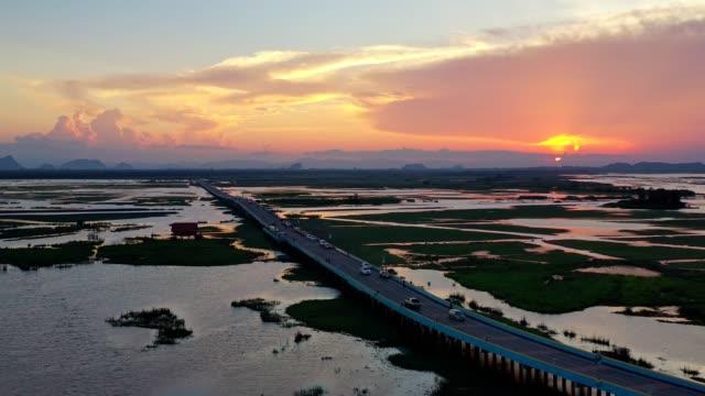 日没の田舎道を走る車の空中風景 - 広角撮影点の映像素材/bロール