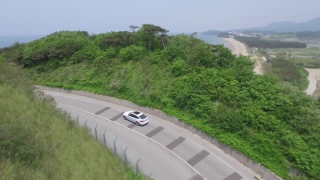 aerial view of car driving along coastal road - land vehicle stock videos & royalty-free footage