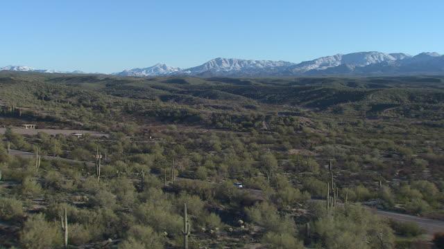 vídeos de stock, filmes e b-roll de vista aérea de carro dirigindo por uma estrada no deserto do arizona, com montanhas de superstição, eua - usa