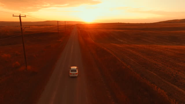 aerial view of car driving down country road at sunset - country road stock videos & royalty-free footage