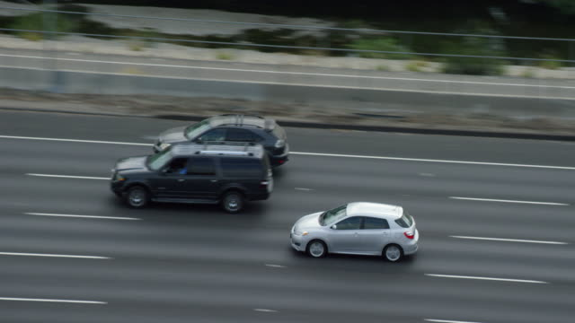 ws ts aerial view of car driving on highway - トラッキングショット点の映像素材/bロール