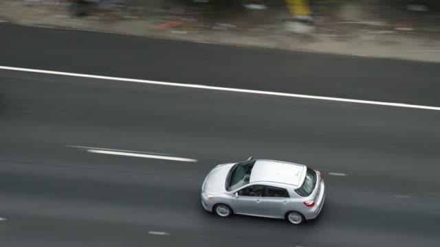 vídeos de stock, filmes e b-roll de ms ts aerial view of car driving on highway - câmera seguindo movimento