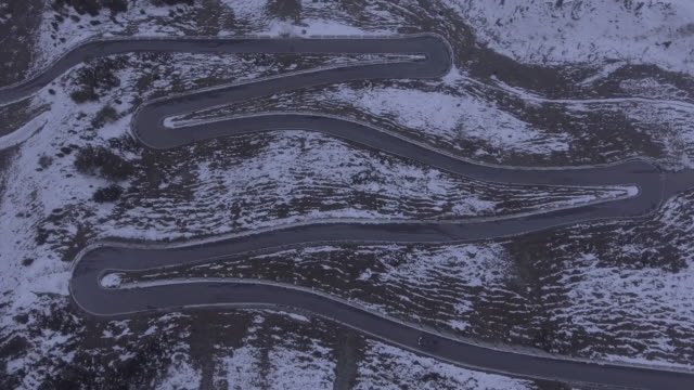 Aerial view of car moving on winding road amidst snow covered mountain, Stelvio Pass, Italy