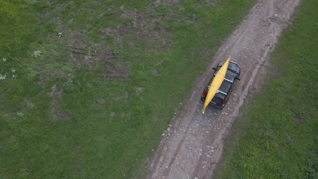 aerial view of car with kayak driving on dirt road. local road trip. - pinaceae stock videos & royalty-free footage