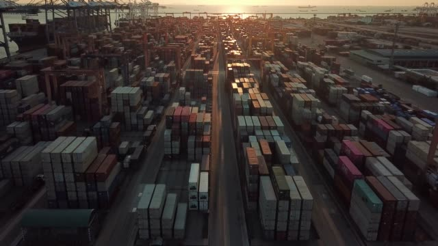 Aerial view of Cargo Container in Commercial Dock at Sunset, Zoom out