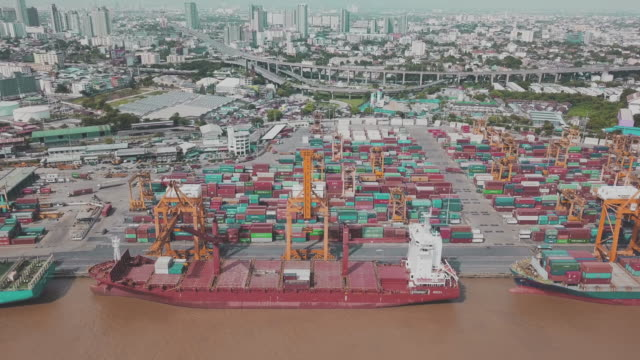 Aerial view of cargo ship moving load at port. 4K